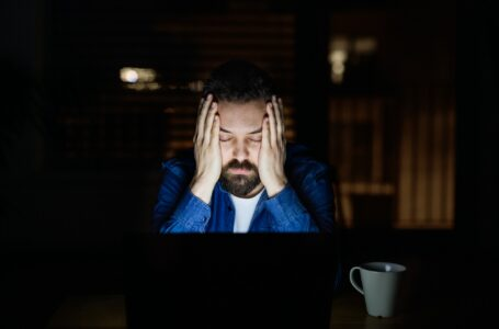 A tired man with laptop at home at night.