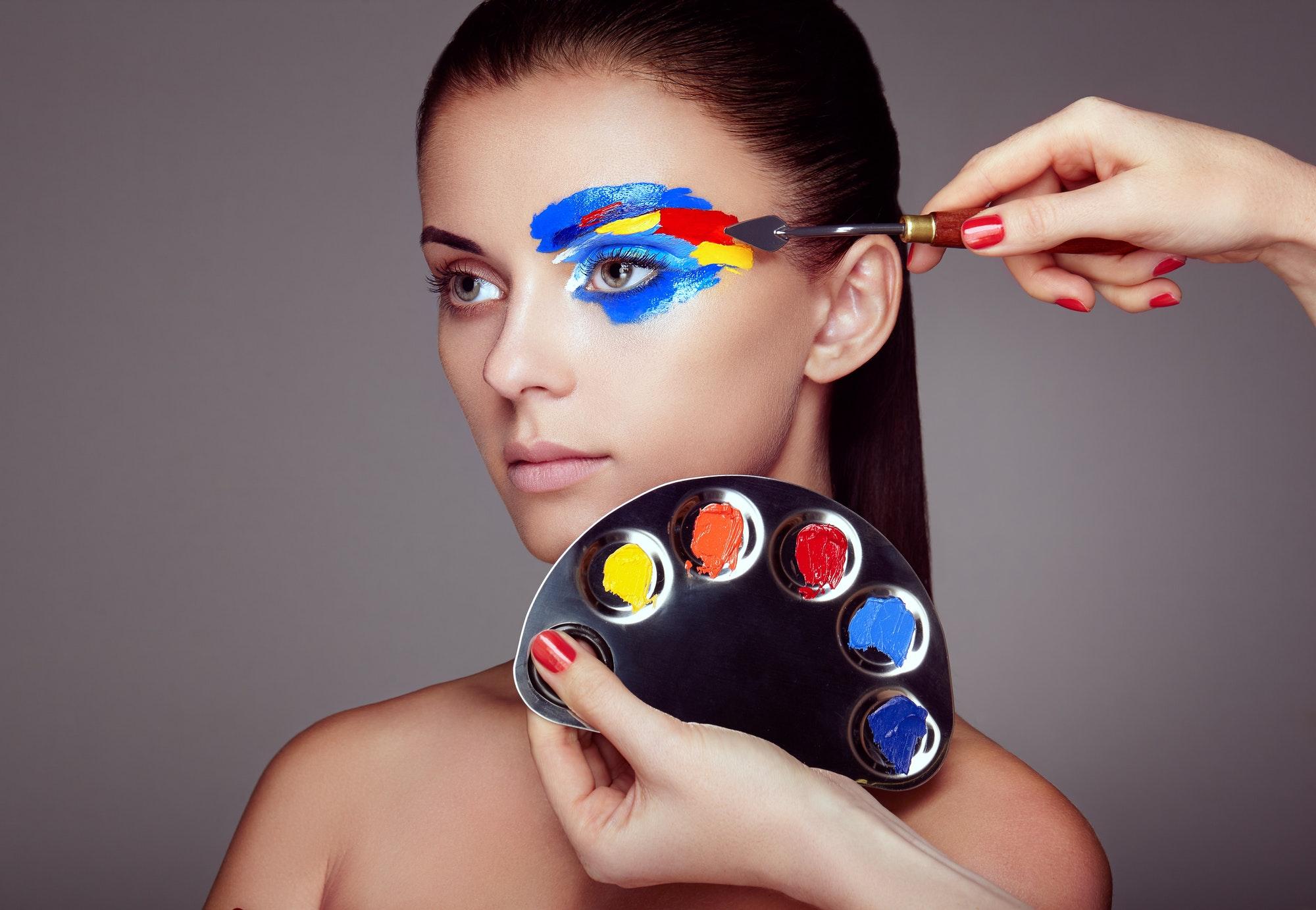 Makeup artist applies colorful makeup