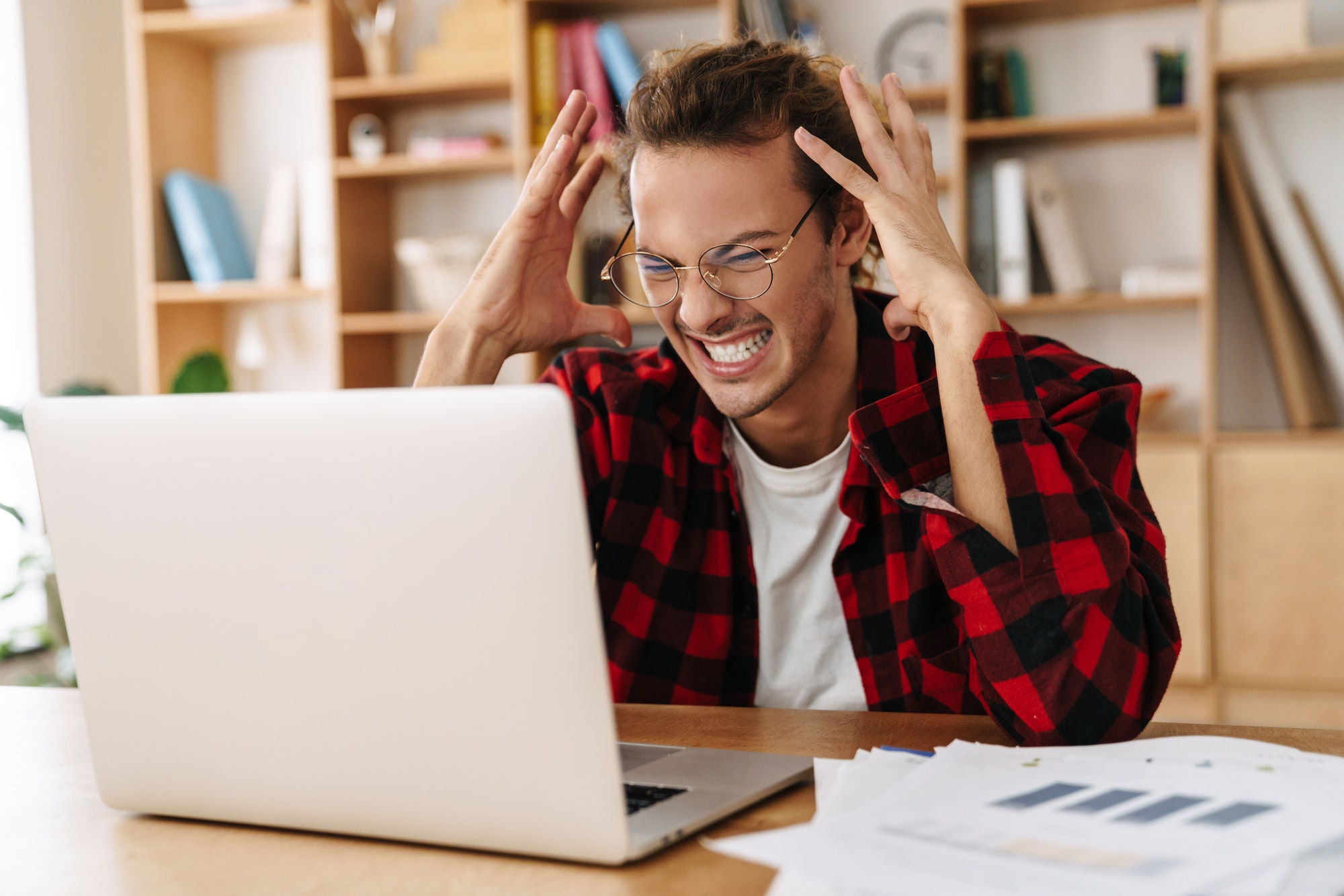 Handsome irritated guy working with laptop while sitting at office