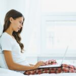 Side view of young woman sitting on bed in bedroom and typing on laptop. Work from home