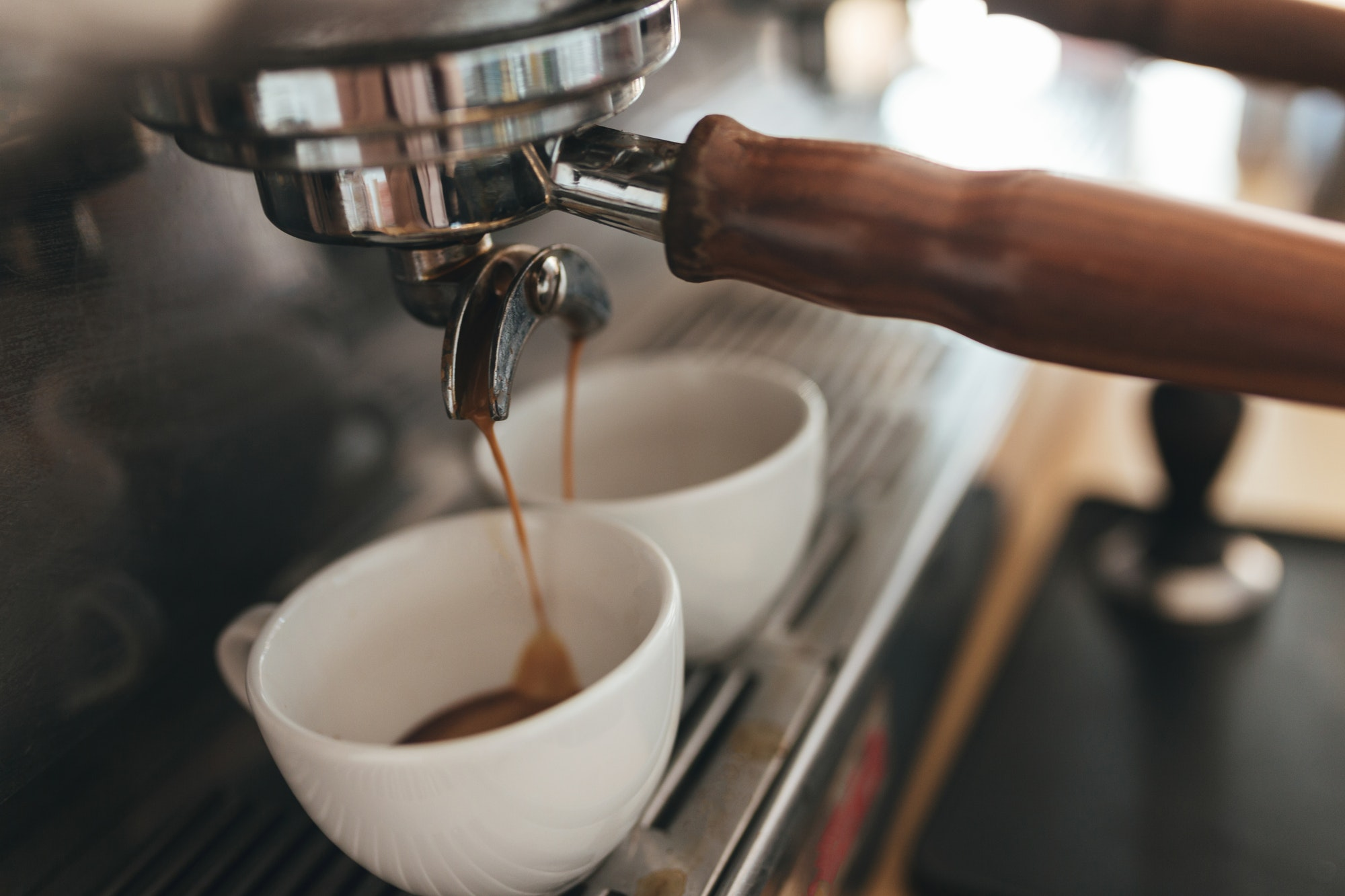 Coffee machine making coffee and pouring into white cups in coffee shop
