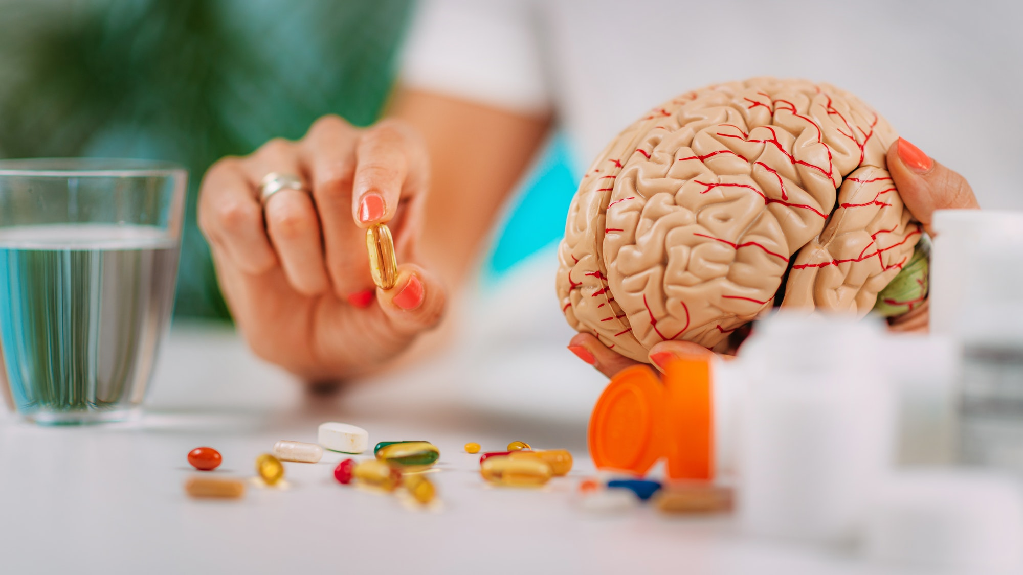 Cognitive improvement or brain supplements. Woman holding a supplement capsule and a model brain.
