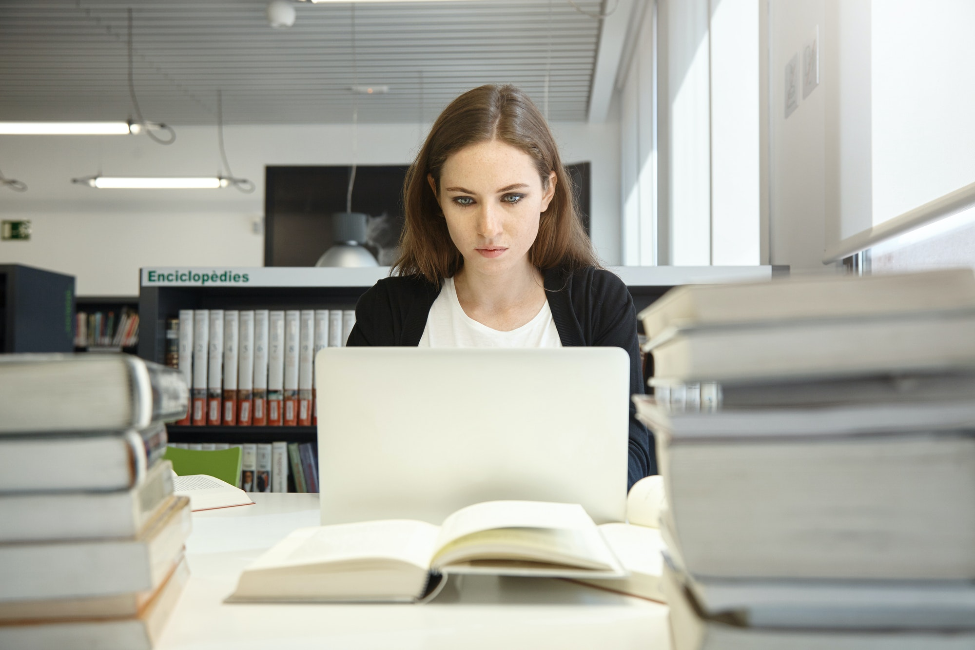Female college student with long hair studying at university library or study room, typing on generi
