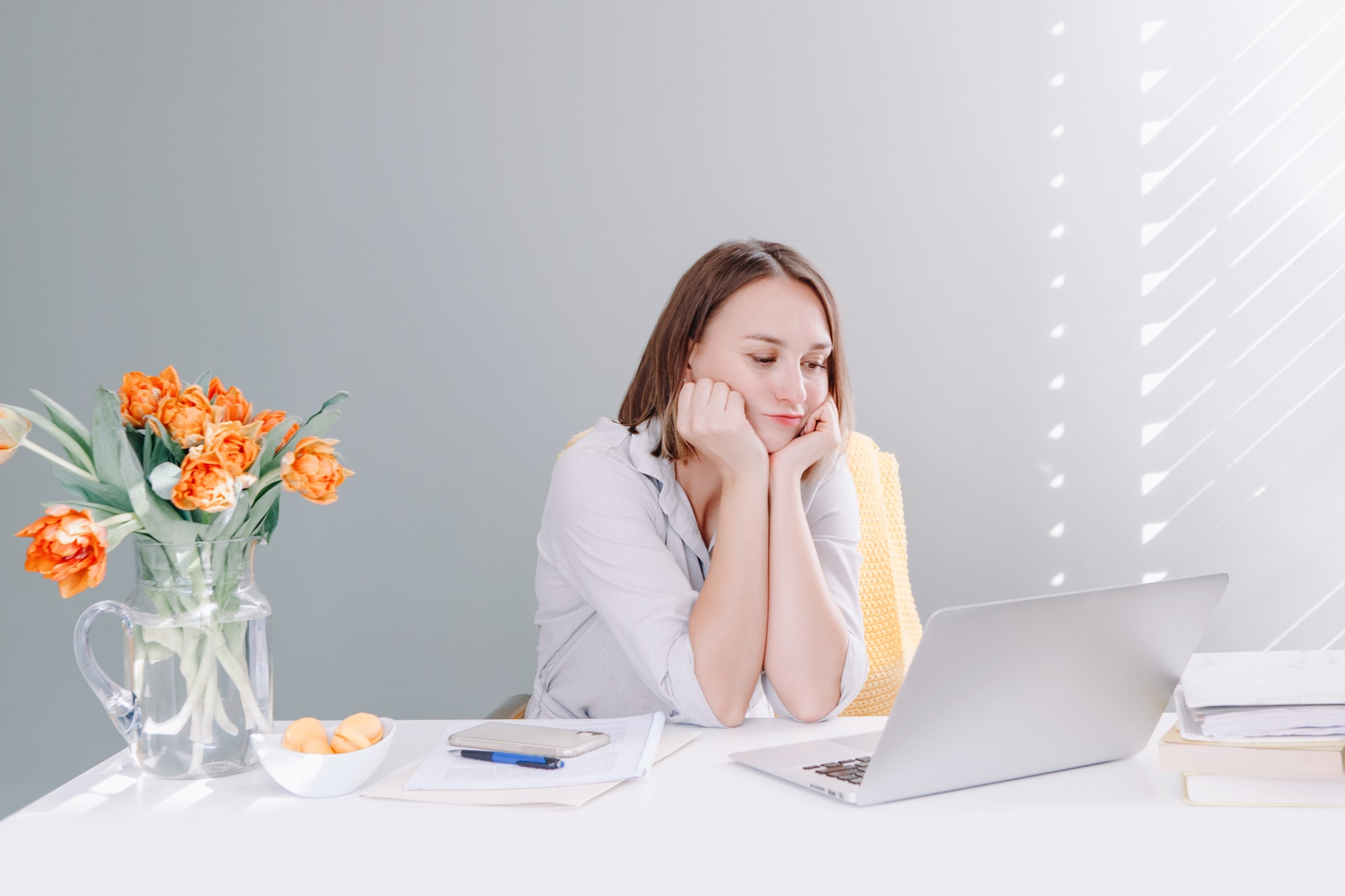 Puzzled overwhelmed business woman working on laptop from home office. Tired bored woman.