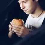 The young man eats hamburger in the car