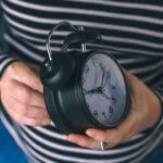 Woman winding retro alarm clock