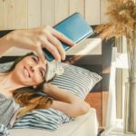 Woman with phone make selfie in bed.