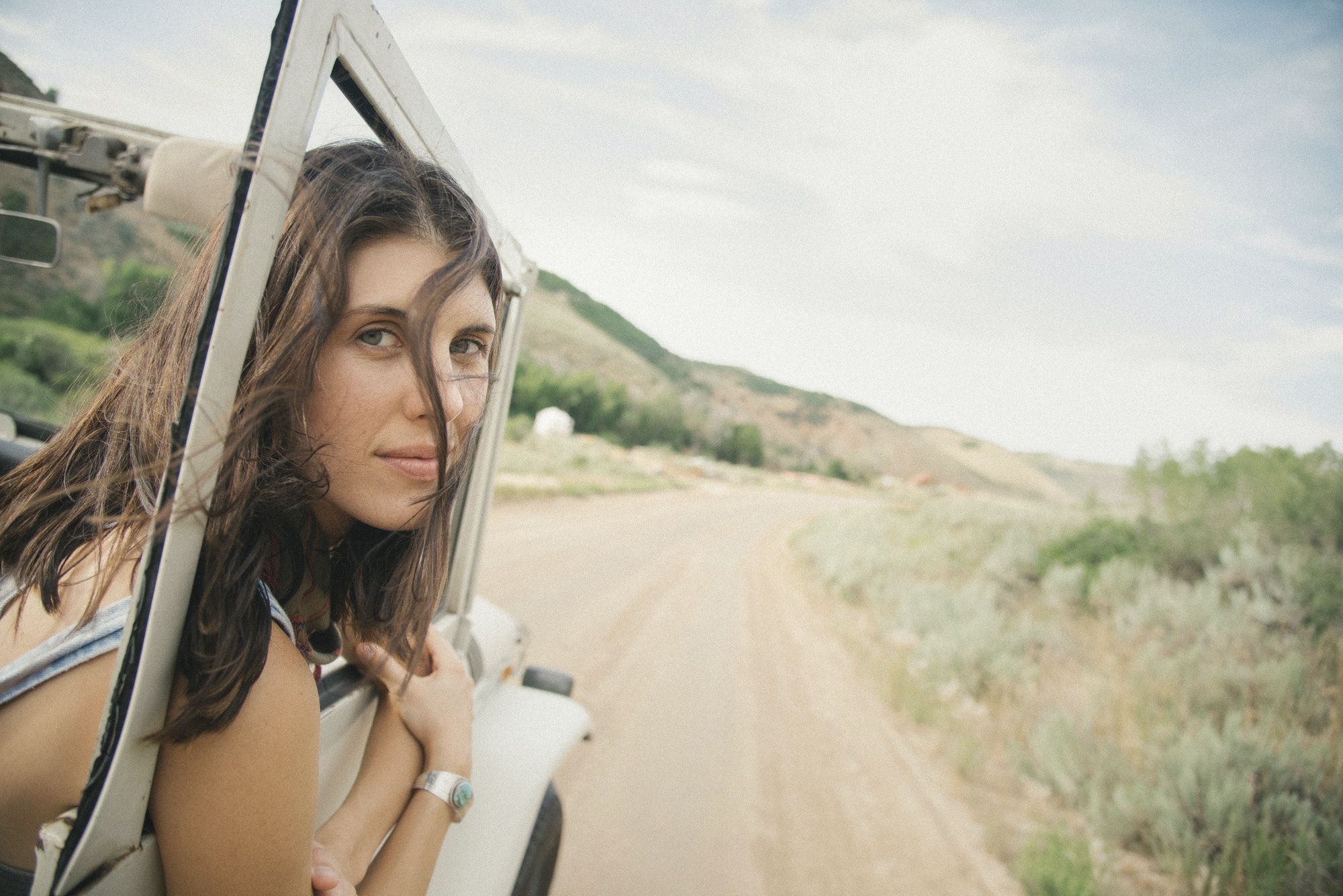 A woman leaning out of a moving jeep on a mountain road.