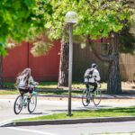 College students riding bicycles through campus on a sunny spring day