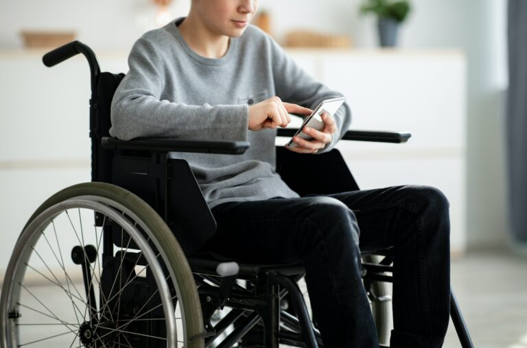 Cropped view of disabled teen boy in wheelchair using smartphone at home, closeup