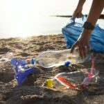 Female Volunteer Cleaning Polluted Beach Collecting Plastic Trash Outdoor, Cropped