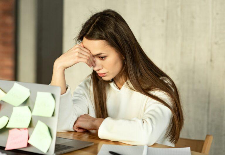 Multitasking freelance Concept. Tired girl holds head
