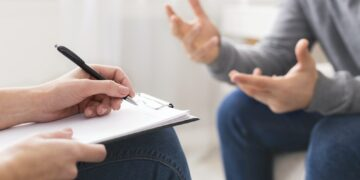 Psychotherapist writing notes, giving diagnosis to emotional man
