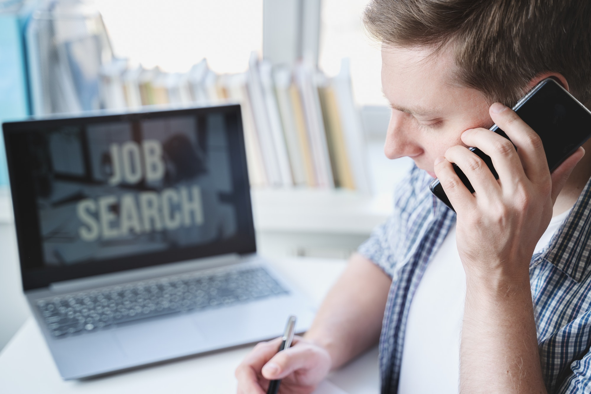 Remote job search. Man speaks on mobile phone, appoints interview for vacancy, writes meeting date