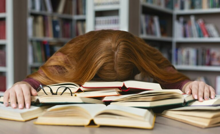 Tired redhead girl sleeping on books at campus library