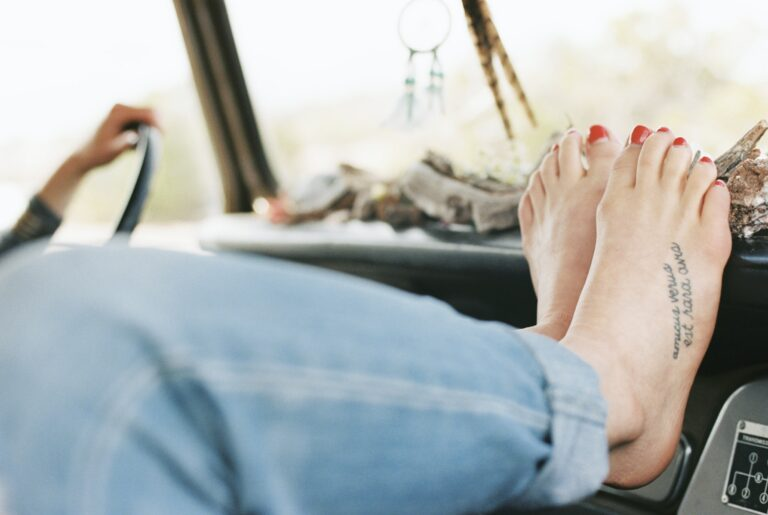 Barefoot woman resting her feet on the dashboard of a 4x4, a tattoo on her right foot.