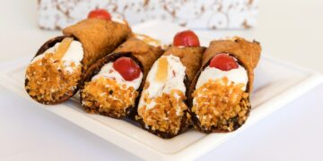 Four Sicilian cannoli with ricotta and pieces of candied pumpkin