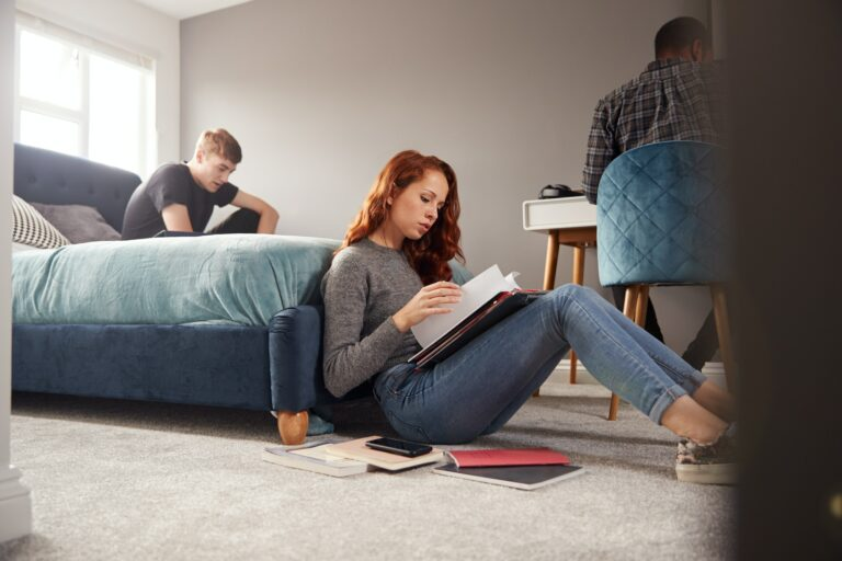 Group Of College Students In Shared House Bedroom Studying Together