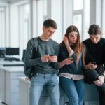 Internet addiction. Group of young people in casual clothes have a rest in the modern office