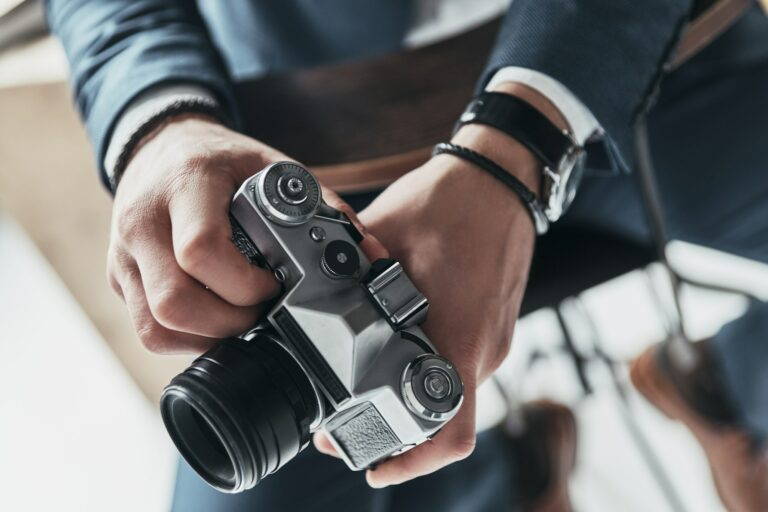 Photography is his passion. Close-up of young man holding a photo camera while sitting on the stool