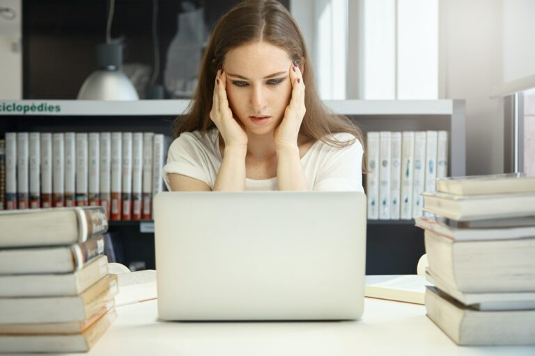 Stressed student girl squeezing her temples with both hands, looking at notebook screen in frustrati