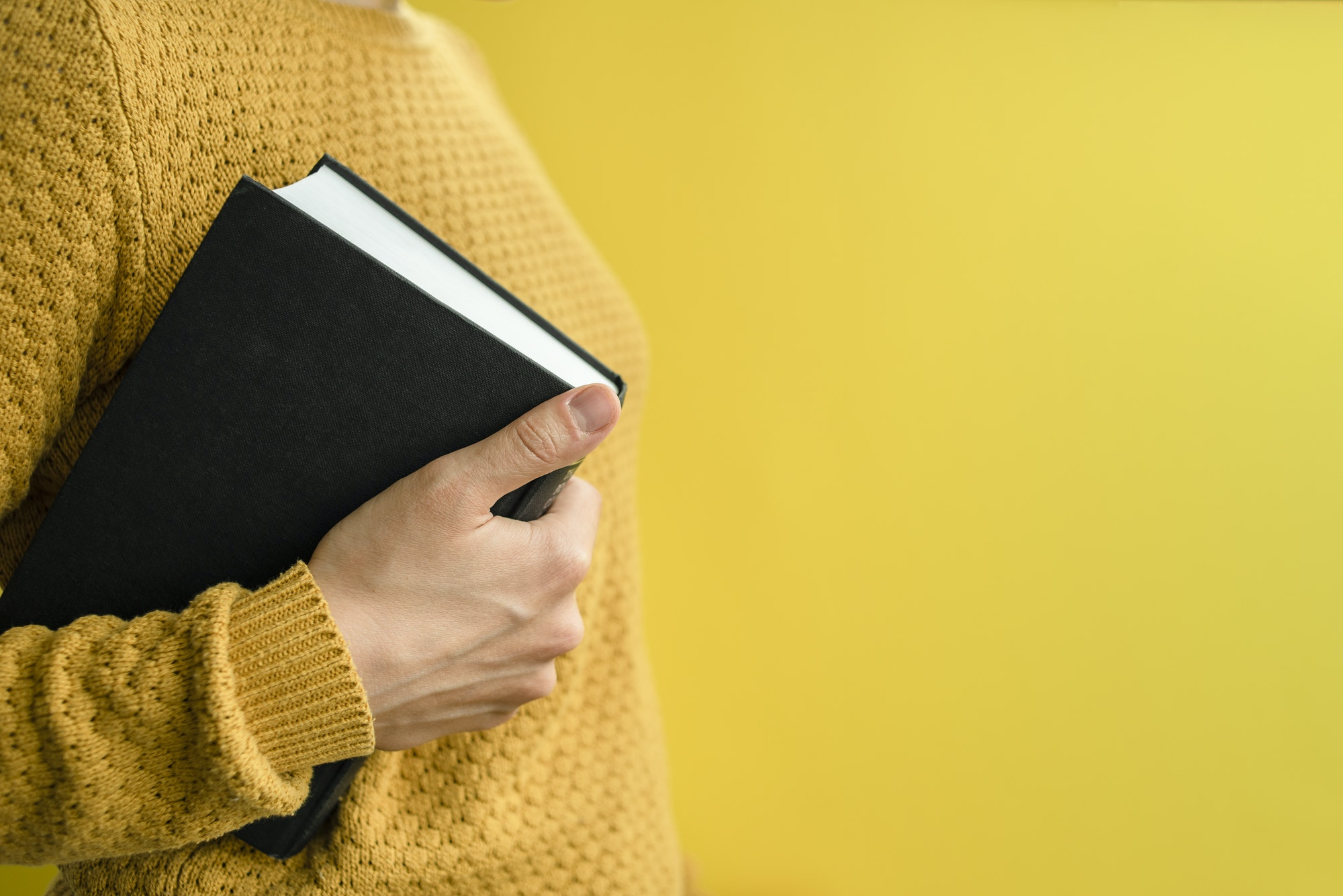 Woman student with books on yellow