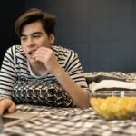 Young man eating chips using laptop in bed