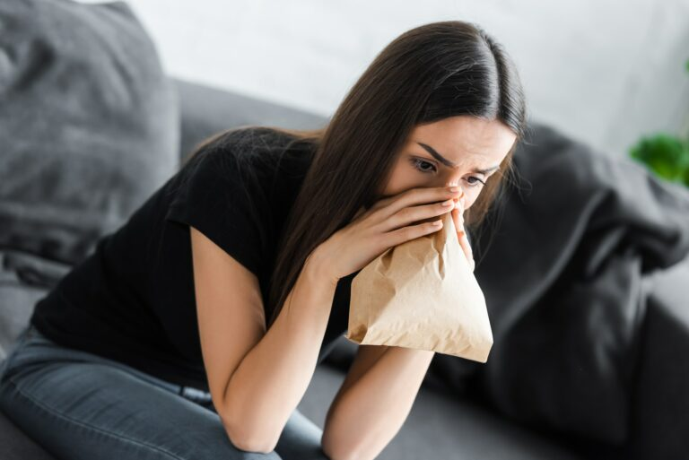 young woman breathing into paper bag while suffering from panic attack at home