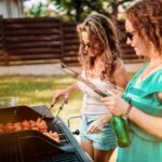 American girls having a backyard barbecue party with friends, laughing and smiling while cooking