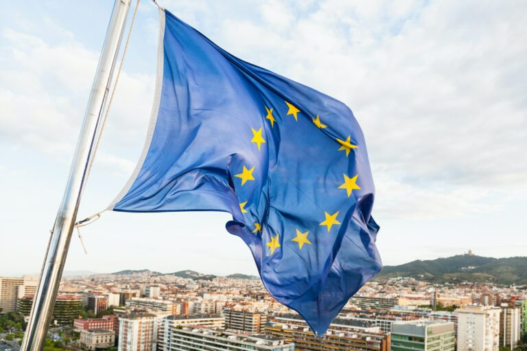 EU flag fluttering by wind above Barcelona