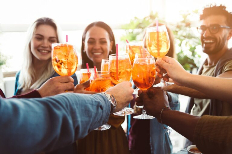 Group of happy friends drinking and toasting friends at a bar restaurant