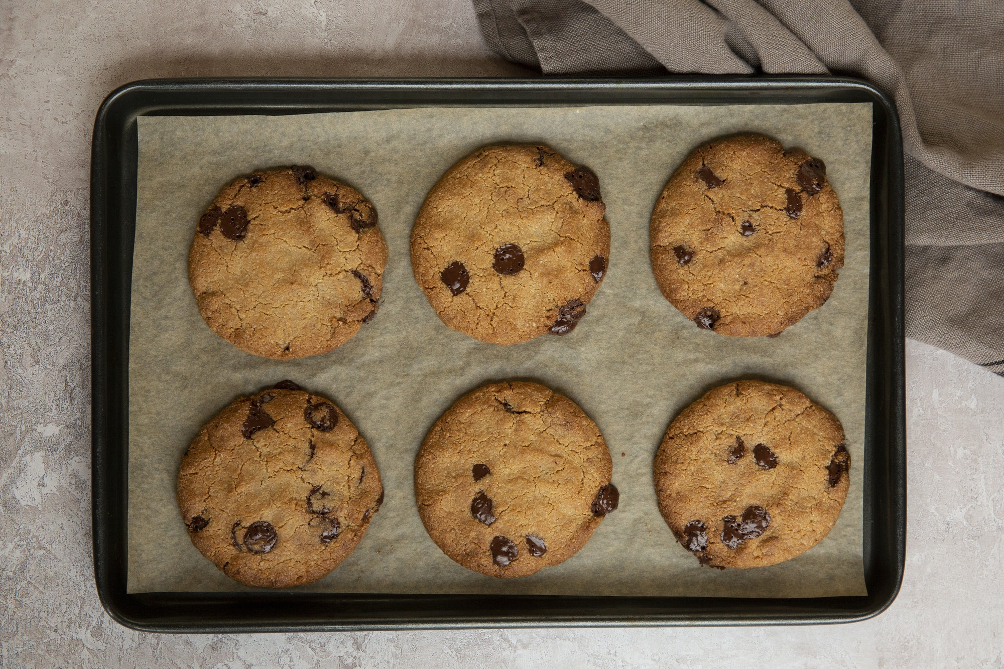 High angle close up of baking tray with freshly baked chocolate chip cookies.