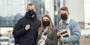 People in a masks stands on the street