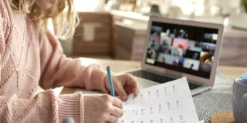 Young female teacher marks exam papers during online classes