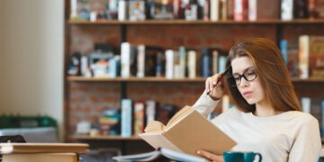 Young woman studying at home with cup of coffee
