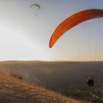 At sunrise in the blue sky paragliders fly in the rays of the golden sun