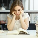 Bored student girl reading a book holding her head in hands, looking concentrated, preparing for the