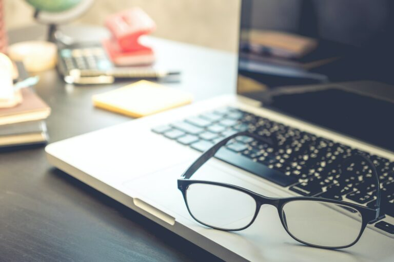 Eyeglasses with laptop on the desk.