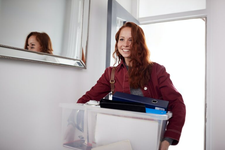 Female College Student Carrying Box Moving Into Accommodation