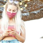 Happy young woman using mobile phone with face mask in beach - Teenager watching video in internet