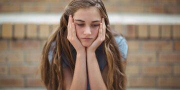 Sad schoolgirl sitting alone in campus