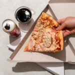 Slice of pizza in a box with Coca-Cola. Home food delivery. Junk food