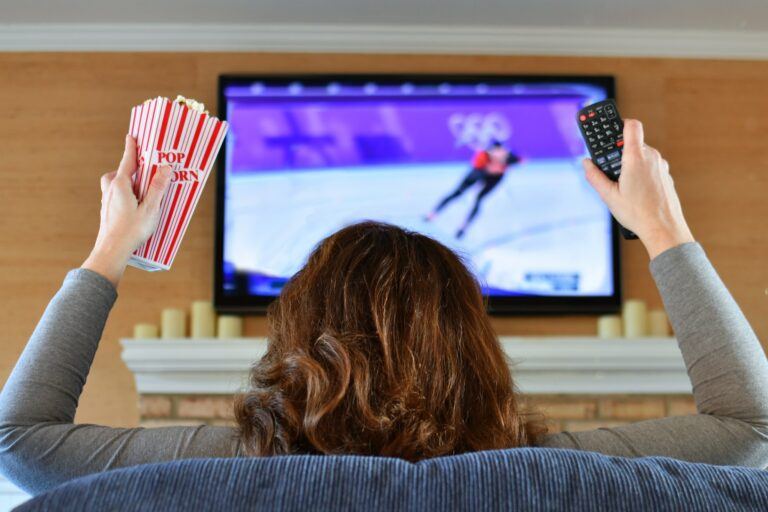 Woman watching sports Olympic speed skating on TV with popcorn and a remote.