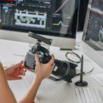 art editor holding digital camera near table with computer monitors