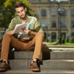 Focused university student doing his homework outside
