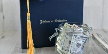 Graduation cap mortarboard tassel on diploma by a jar of money cash, concept school loans debt