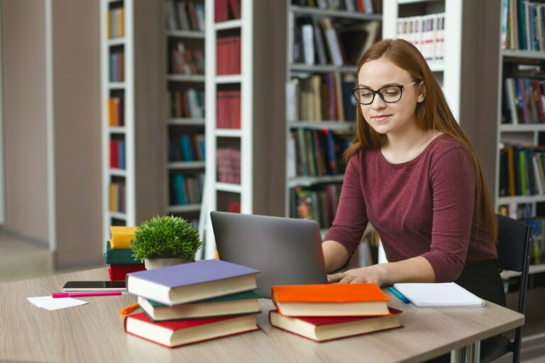 Intelligent redhead girl studying with laptop at library