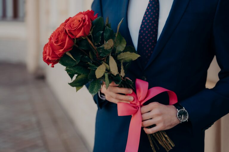 Man dressed in blue suit holding bouquet of red roses