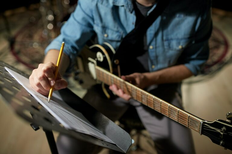 man with guitar writing to music book at studio