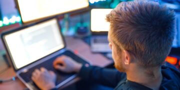 Programmer using laptop and PC, information coding